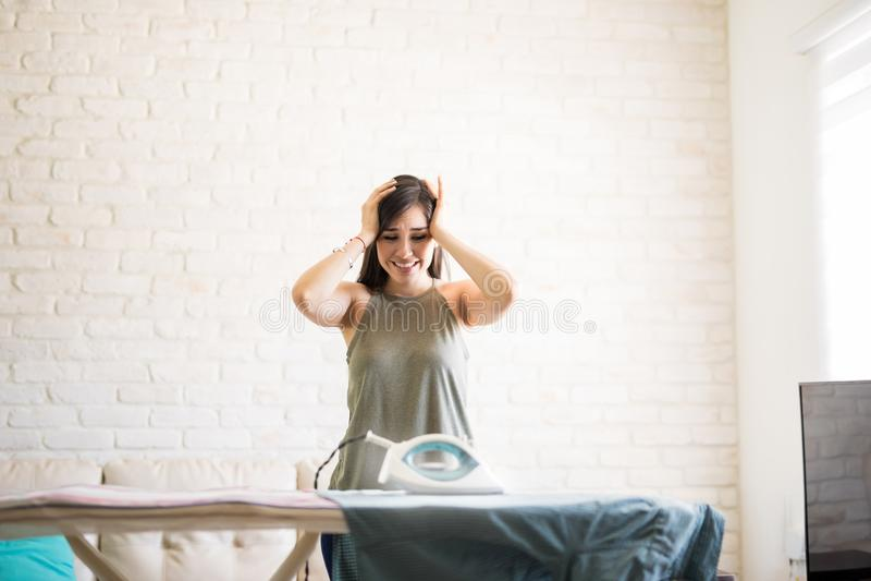 Femme regardant le tissu brûlé tout en se tenant prêt la planche à repasser photo libre de droits