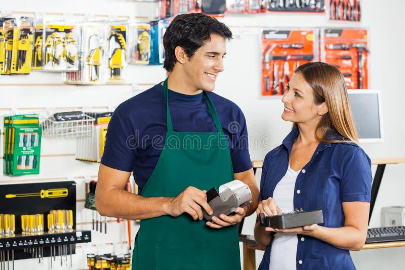 Femme regardant le travailleur frappant à toute volée la carte de crédit photo libre de droits