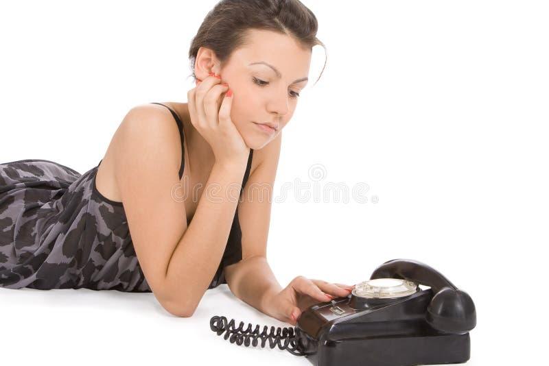 Femme regardant le vieux téléphone attendant un appel images stock