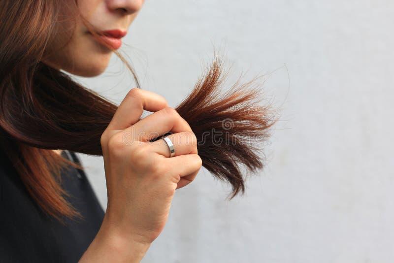 Femme regardant les pointes fourchues endommag?es des cheveux, concept de Haircare images libres de droits
