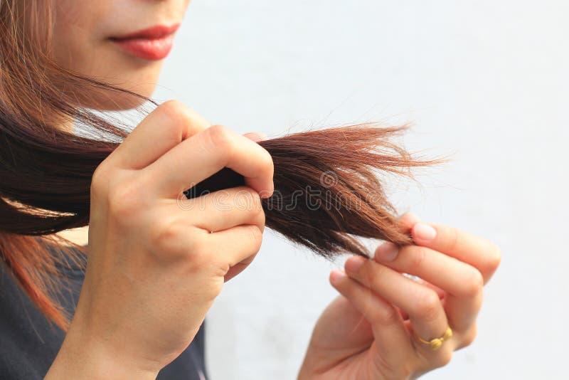 Femme regardant les pointes fourchues endommag?es des cheveux, concept de Haircare photo stock