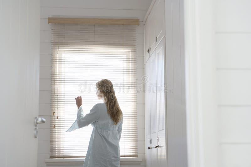 Femme regardant par des abat-jour de fenêtre photographie stock