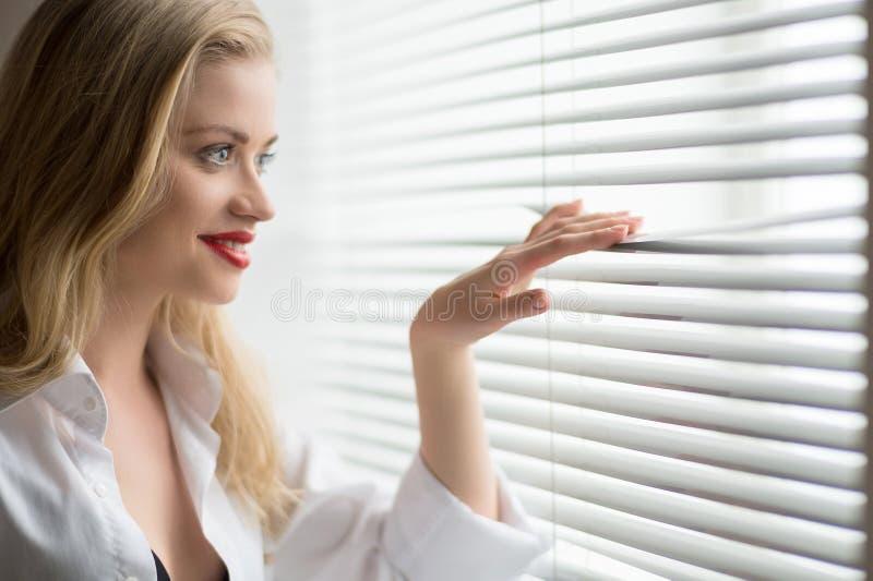 Femme regardant par la fenêtre. photos libres de droits