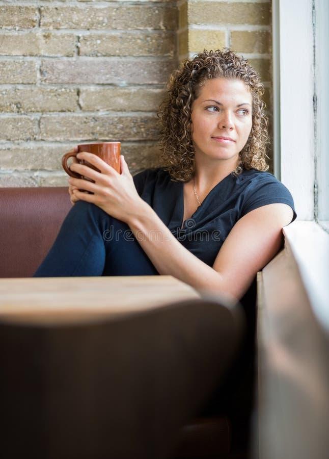 Femme regardant par la fenêtre dans le cafétéria image libre de droits