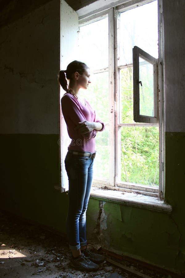 Femme regardant par la vieille fenêtre image stock