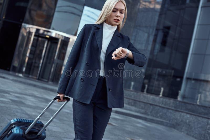 Femme regardant sa montre-bracelet tout en allant au bureau photos libres de droits