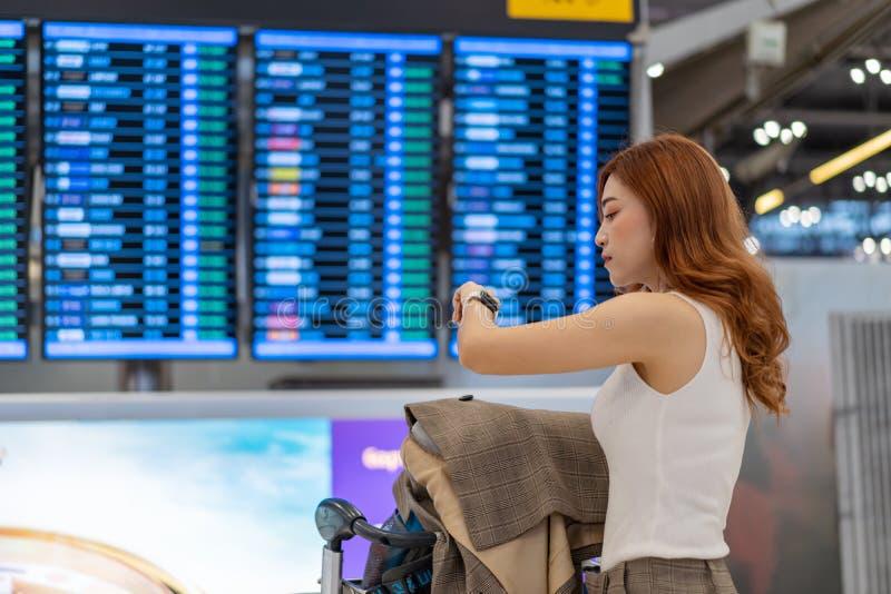 Femme regardant sa montre intelligente avec le conseil de l'information de vol l'aéroport photo stock