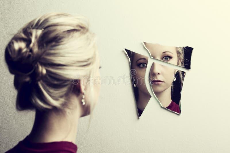 Femme regardant son visage en trois tessons de miroir cassé photographie stock