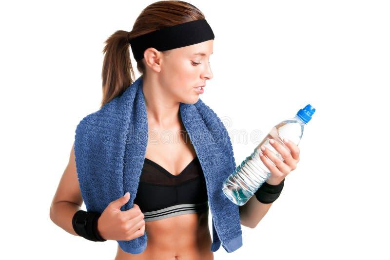 Femme regardant une bouteille de l'eau photo stock