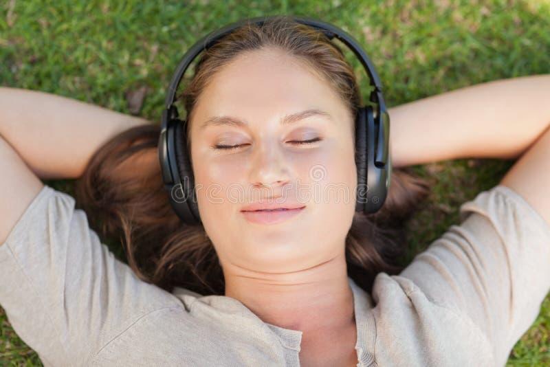 Femme Relaxed se trouvant sur la pelouse photographie stock