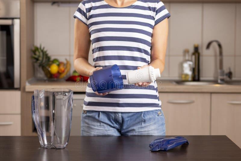 Femme remplaçant le filtre dans un broc de l'eau image libre de droits