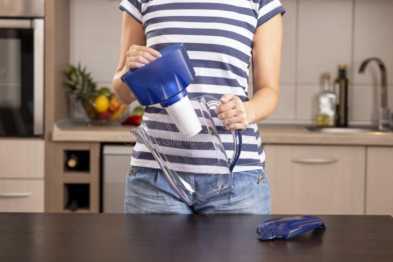 Femme remplaçant un filtre de broc de l'eau images stock