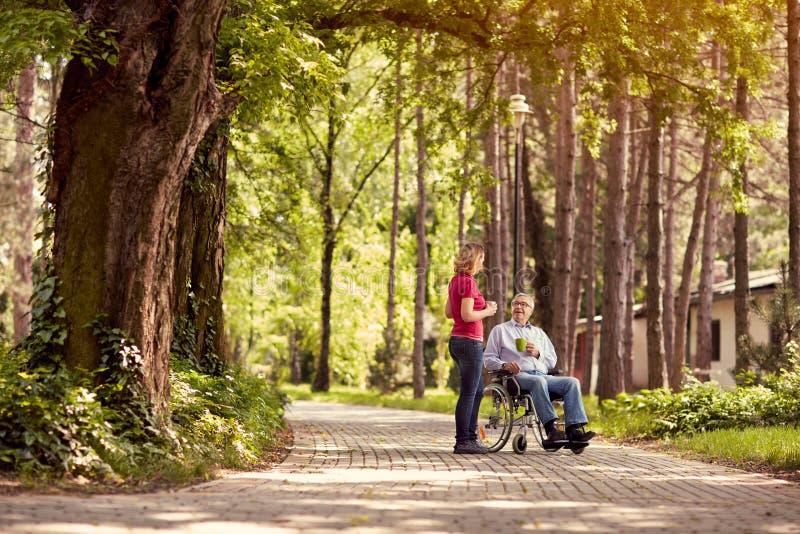 Femme rendant visite à son père handicapé dans le fauteuil roulant et appréciant le Ti photographie stock