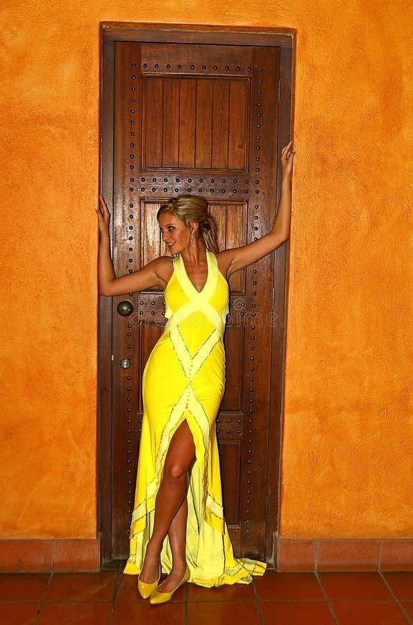 Femme renversant dans la robe jaune photographie stock libre de droits