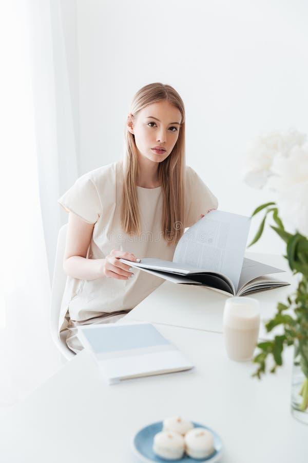 Femme reposant à l'intérieur le livre de lecture regarder l'appareil-photo images libres de droits