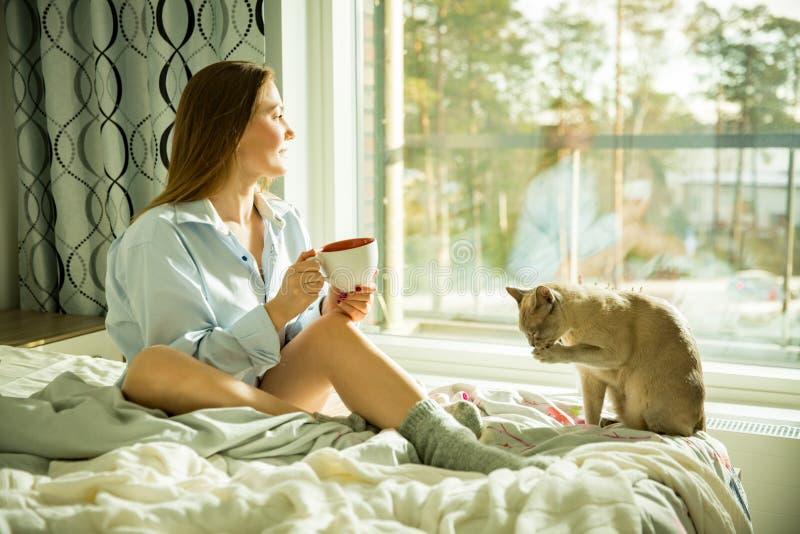 Femme reposant à la maison un lit par la fenêtre avec la tasse de café chaud photos stock