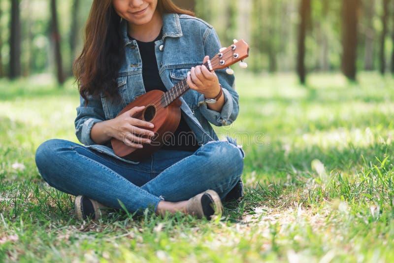 Femme reposant et jouant l'ukulélé dans l'extérieur photos libres de droits