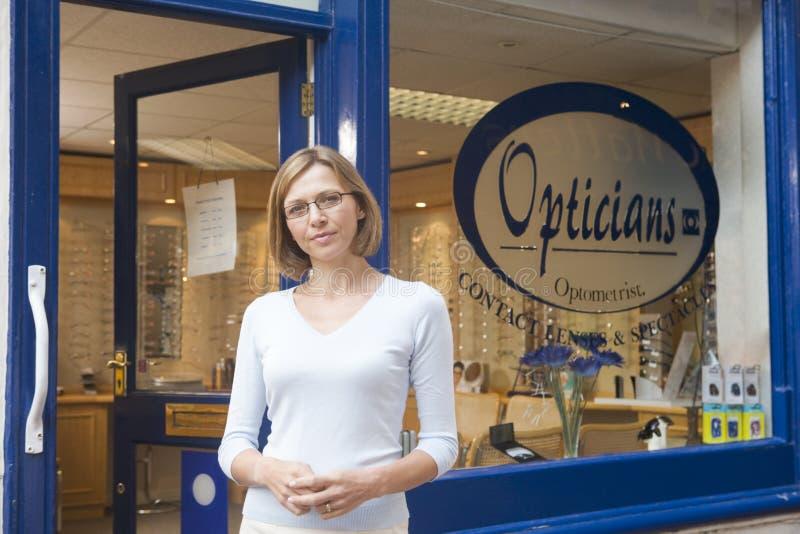 Femme restant à l'avant l'entrée des optométristes photographie stock libre de droits