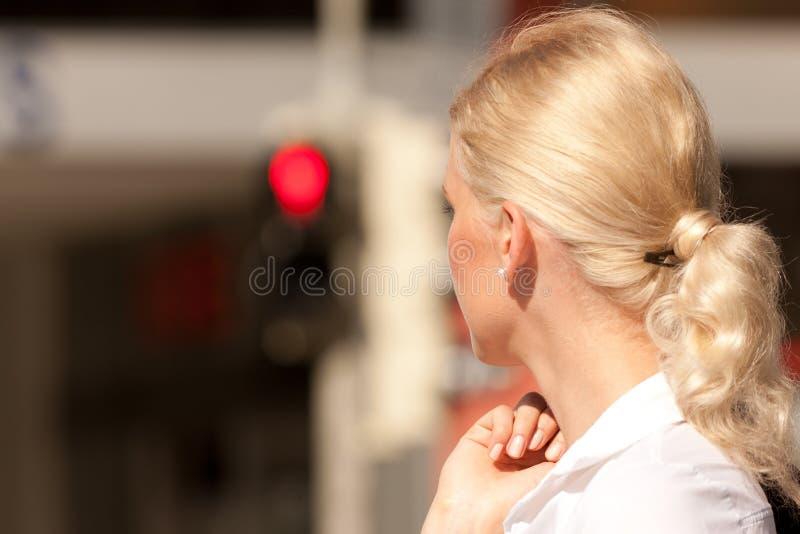 Femme restant au feu de signalisation rouge images stock