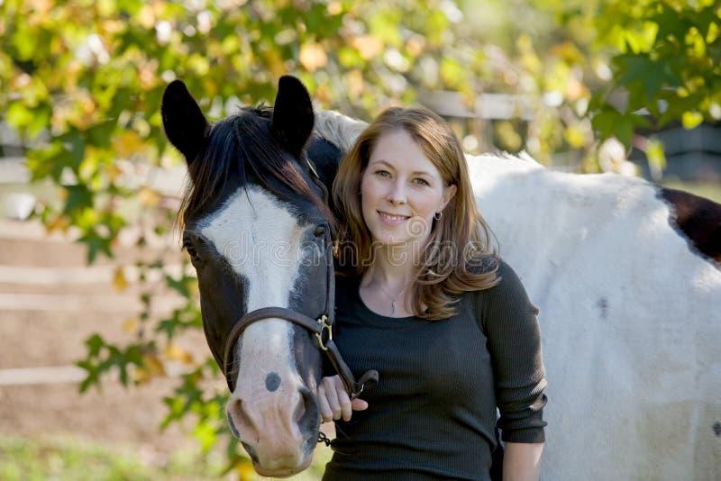 Femme restant avec le cheval photo stock