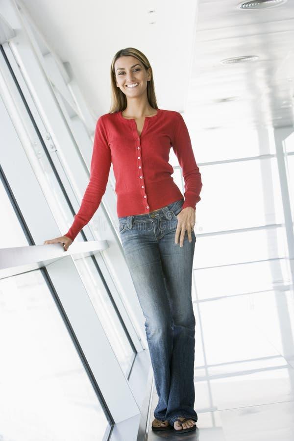 Femme restant dans le sourire de couloir photo stock