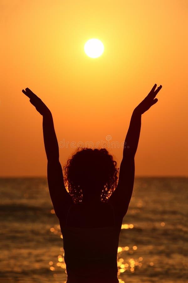 Femme restant sur la plage, mains d'augmenter image libre de droits