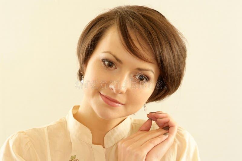 Femme restant sur un fond beige images stock