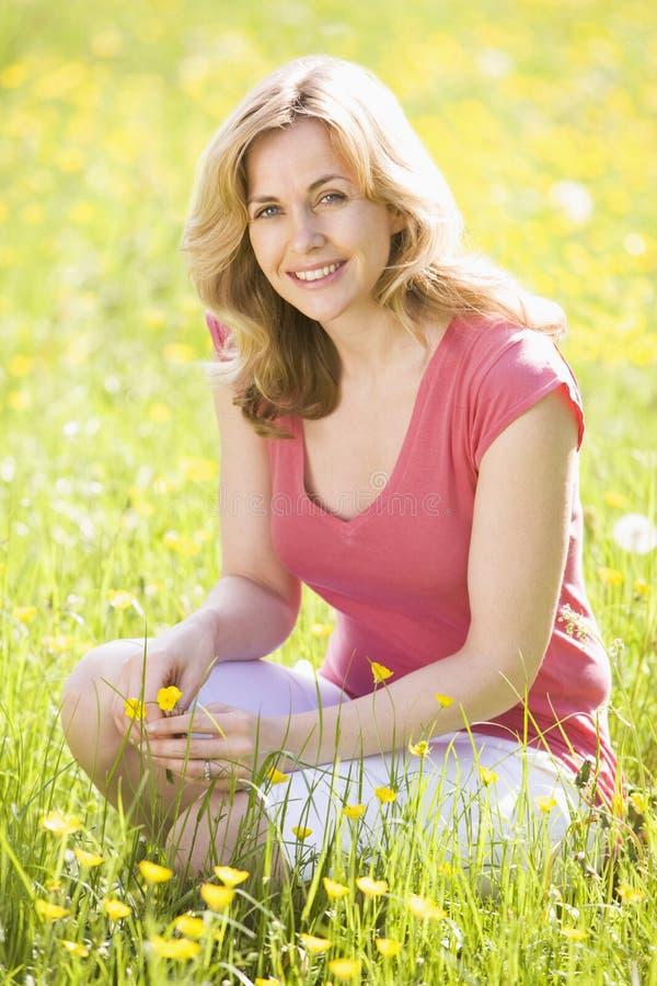 Femme retenant à l'extérieur le sourire de fleur photos libres de droits