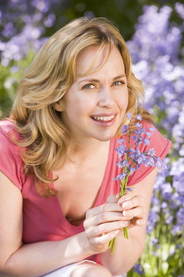 Femme retenant à l'extérieur le sourire de fleurs image stock