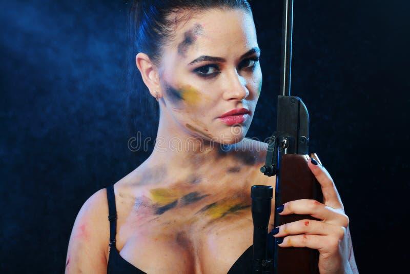 Femme retenant l'arme photographie stock