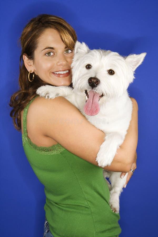 Femme retenant le crabot blanc de chien terrier. image stock