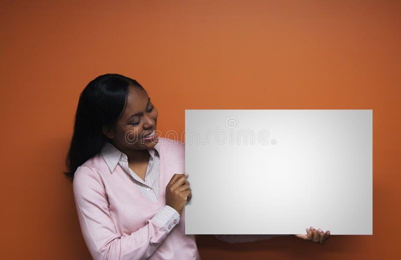 Femme retenant le signe blanc photographie stock