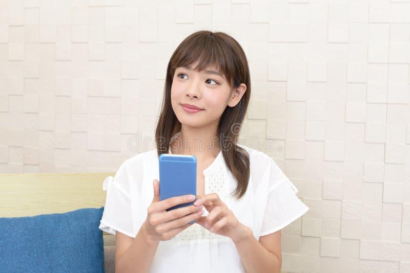 Femme retenant un t?l?phone intelligent image libre de droits