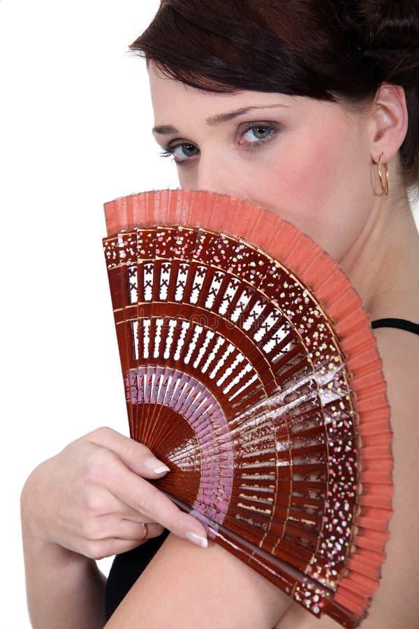 Femme retenant un ventilateur photos stock