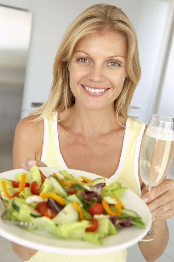 Femme retenant une glace de vin et une salade fraîche photo libre de droits