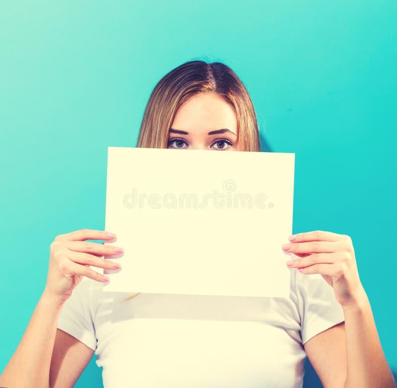 Femme retenant une page de papier blanche photographie stock libre de droits