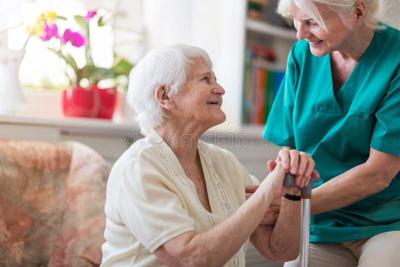 Femme retirée de sourire avec le soignant à la maison féminin photographie stock