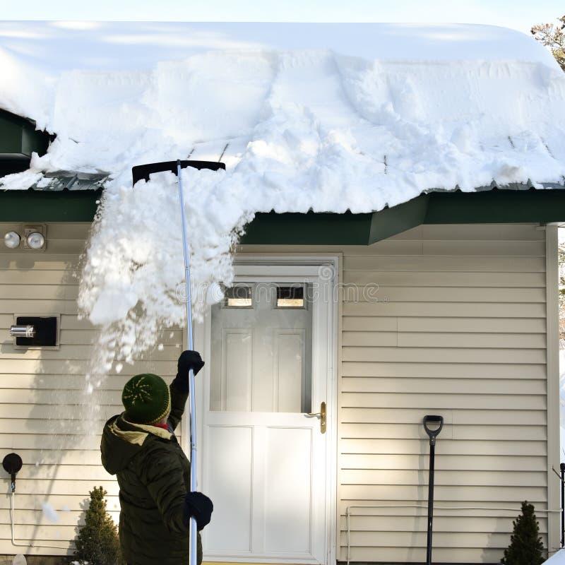 Femme retirant la neige du toit avec le râteau de neige photo stock