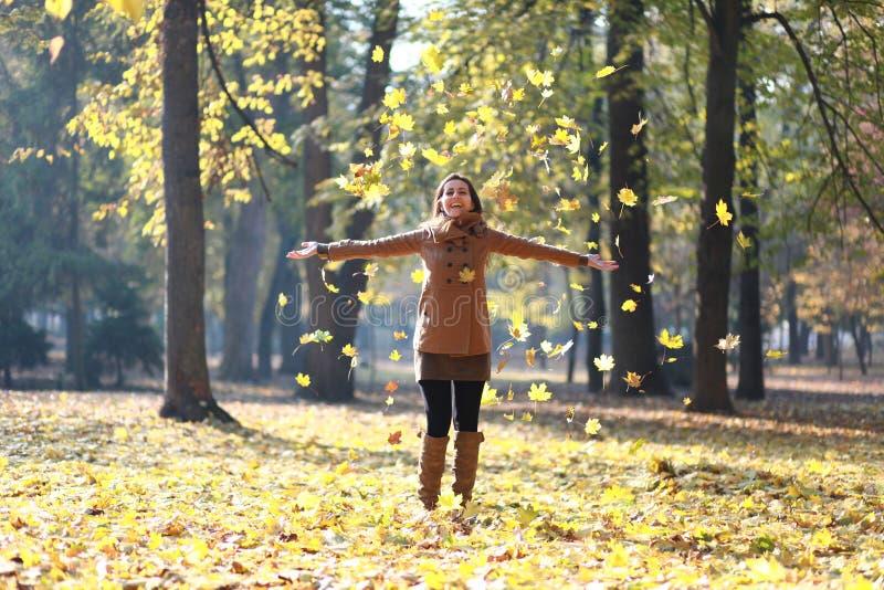 Femme riant après le lancement des feuilles image libre de droits