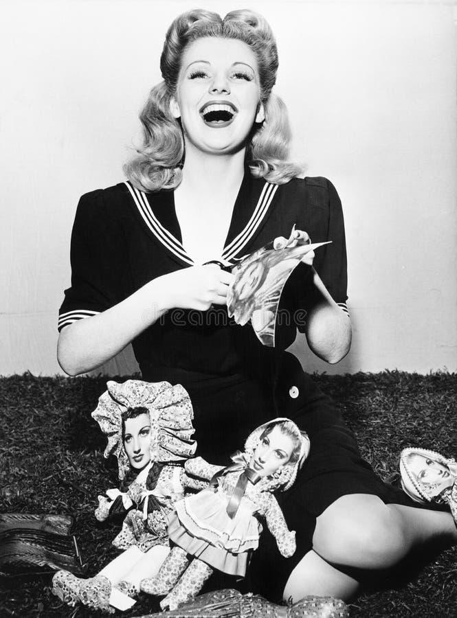 Femme riant et coupant les visages de papier de poupées (toutes les personnes représentées ne sont pas plus long vivantes et aucu photo stock