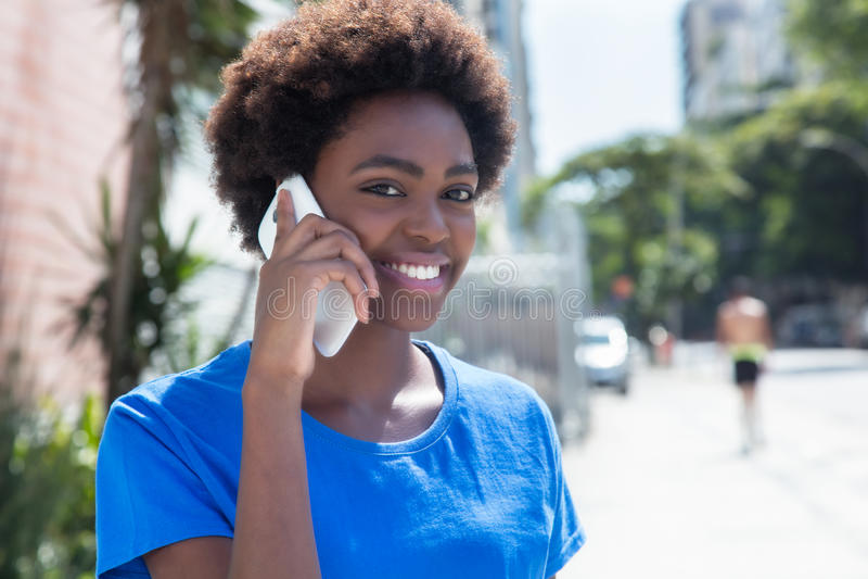 Femme riante d'afro-américain dans une chemise bleue au téléphone photo stock