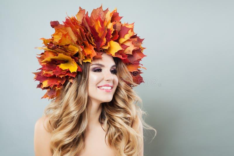 Femme riante dans des feuilles d'automne sur le fond gris Le beau modèle avec composent, longtemps les cheveux bouclés, la peau c images stock