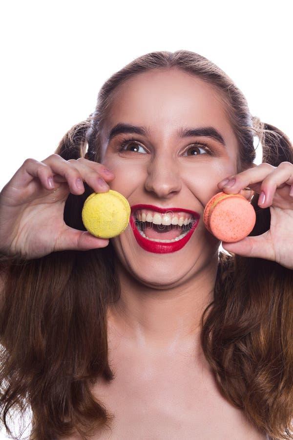Femme riante de brune avec le maquillage lumineux tenant le macaroo doux image libre de droits