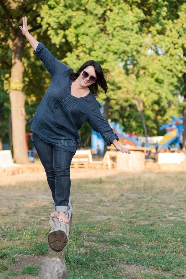 Femme riante marchant sur le rondin avec sa diffusion de bras image stock
