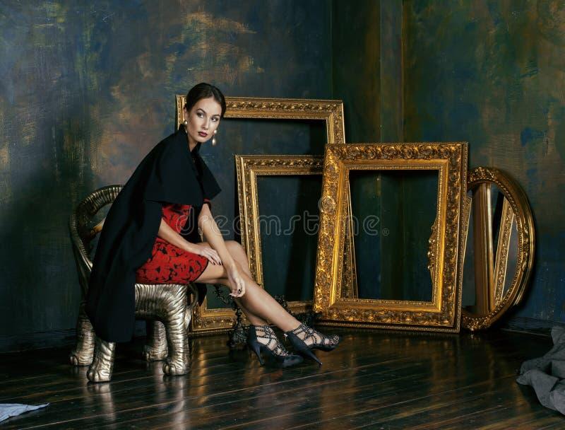 Femme riche de brune de beauté dans proche intérieur de luxe photographie stock