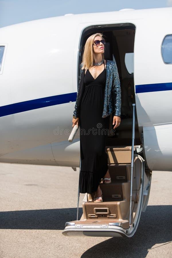 Femme riche faisant un pas hors du jet privé photo libre de droits