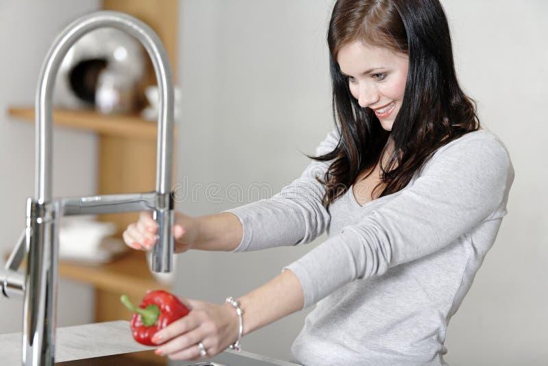 Femme rinçant des poivrons dans un évier photos libres de droits