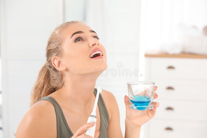 Femme rinçant la bouche avec le collutoire dans la salle de bains soin de h images libres de droits