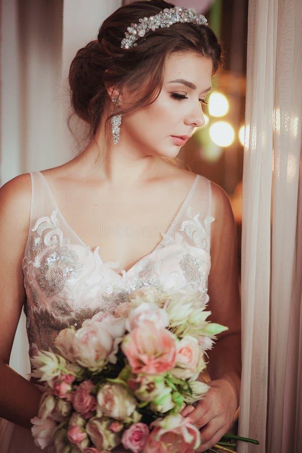 Femme romantique dans la robe nuptiale rose avec le bouquet de mariage se tenant contre la lumière Regard vers le bas D'intérieur image stock