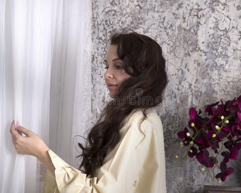 Femme romantique se tenant à la fenêtre photo libre de droits
